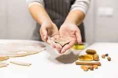 Молодая милая женщина подготавливает тесто и печет пряник и печенья в кухне Она держит отрезок звезды от стоковое изображение rf