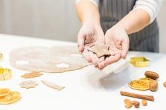 Молодая милая женщина подготавливает тесто и печет пряник и печенья в кухне Она держит отрезок звезды от стоковое фото rf