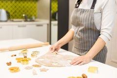 Молодая милая женщина подготавливает тесто и печет пряник и печенья в кухне Она делает форму звезды на стоковые фото