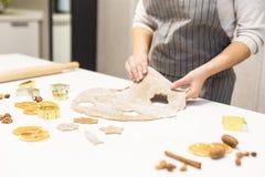 Молодая милая женщина подготавливает тесто и печет пряник и печенья в кухне Она делает форму звезды на стоковые изображения