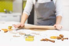 Молодая милая женщина подготавливает тесто и печет пряник и печенья в кухне E стоковое изображение