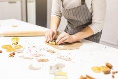 Молодая милая женщина подготавливает тесто и печет пряник и печенья в кухне Она делает форму звезды на стоковое фото