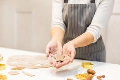 Молодая милая женщина подготавливает тесто и печет пряник и печенья в кухне Она держит отрезок звезды от стоковые фото