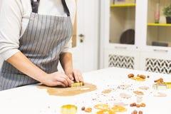 Молодая милая женщина подготавливает тесто и печет пряник и печенья в кухне Она делает форму звезды на стоковые фотографии rf