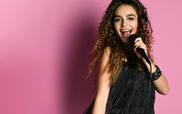 Молодая милая женщина поя в конце микрофона вверх стоковая фотография rf