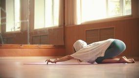 Молодая милая женщина работая на циновке йоги - выполнять работать для поясницы и позвоночника сток-видео