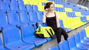 Молодая милая женщина сидит на трибуне стадиона акции видеоматериалы