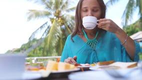 Молодая милая женщина сидя в кафе пляжа имеет кофе пить завтрака стоковое фото rf