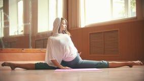 Молодая милая женщина сидя на циновке йоги выполняя разделение - делающ ногу протягивая тренировки - студия танца акции видеоматериалы