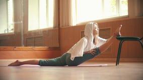 Молодая милая женщина сидя на циновке йоги выполняя разделение - делающ ногу протягивая тренировки используя стул - танец видеоматериал