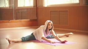 Молодая милая женщина сидя на циновке йоги выполняя разделение - делающ протягивающ тренировки с гнуть к стороне и акции видеоматериалы