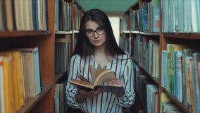 Молодая милая женщина со стеклами в удерживании библиотеки книга в ее руке, листая через страницы акции видеоматериалы