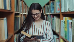 Молодая милая женщина со стеклами в удерживании библиотеки книга в ее руке, листая через страницы Смех девушки акции видеоматериалы
