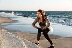 Молодая милая женщина спорта при наушники делая тренировку простирания стоковые фотографии rf
