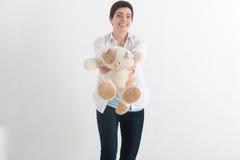 Молодая милая женщина с короткими волосами в непринужденном стиле давая переднего кота игрушки плюша и смотря камеру с улыбкой зу Стоковая Фотография RF