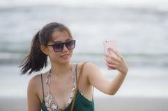 Молодая милая и сладостная китайская азиатская женщина на пляже принимая портрет изображения selfie с камерой мобильного телефона Стоковая Фотография RF