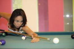 Молодая милая и счастливая азиатская девушка играя снукер держа ручку на бильярдном столе в ночном клубе или баре Стоковые Фото