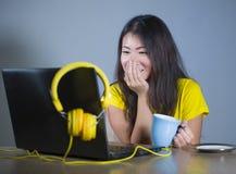 Молодая милая и счастливая азиатская корейская женщина на столе наслаждаясь интернетом на портативном компьютере усмехаясь смотря стоковая фотография