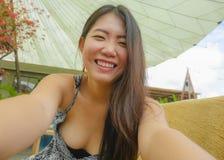 Молодая милая и счастливая азиатская корейская туристская женщина усмехаясь держащ мобильный телефон или камера фотографируя self стоковое фото rf