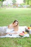 Молодая милая книга чтения девушки и лежать на шотландке около плодов и шляпы, травы в предпосылке стоковые изображения rf