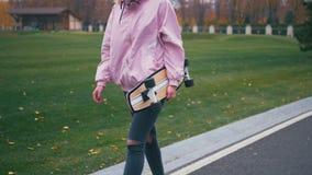 Молодая милая красивая белокурая женщина хипстера идя вниз с дороги с longboard скейтборда в замедленном движении сток-видео