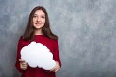 Молодая милая усмехаясь девушка в красном свитере против backgro стоковые изображения