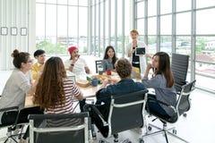 Молодая многонациональная разнообразная творческая азиатская группа говоря или коллективно обсуждать в мастерской встречи офиса с стоковые фото