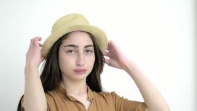 Молодая модельная девушка в предпосылке студии белой конец вверх по красивой кавказской даме во взглядах шляпы на камере акции видеоматериалы