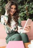 Молодая модная женщина используя мобильный телефон стоковое изображение rf