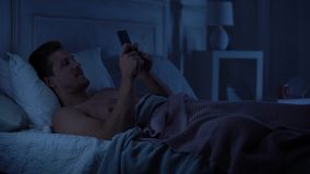 Молодая мужская отправка SMS на смартфоне и усмехаться, беседующ с девушкой, устройство видеоматериал