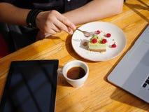 Молодая мужская рука и вкусное пирожное с чашкой поленик cofe с молоком и таблеткой на деревянном столе Бизнес Стоковые Изображения RF