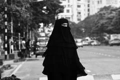 Молодая мусульманская дама идя в фото улиц города уникально стоковая фотография