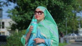 Молодая мусульманская женщина в светлом шарфе и солнечных очках в парке выпивает кофе видеоматериал