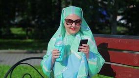 Молодая мусульманская женщина в светлом шарфе и солнечных очках сидит на стенде в парке и выпивая кофе и говорить сток-видео