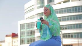 Молодая мусульманская женщина в светлом шарфе на предпосылке современного здания видеоматериал