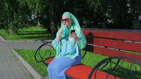 Молодая мусульманская женщина в светлом шарфе полиняна на стенде в парке и кофе напитков и беседах в посыльном сток-видео