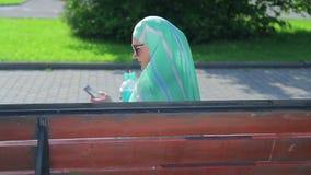 Молодая мусульманская женщина в светлом шарфе сидит на стенде в парке и кофе напитков и беседах в посыльном Сторона сток-видео