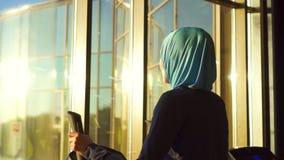 Молодая мусульманская женщина в hijab делая спорт на имитаторе перед окном видеоматериал