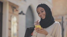 Молодая мусульманская женщина в hijab ища продаж в смартфоне, стоя вниз по улице с хозяйственными сумками в ее руке сток-видео