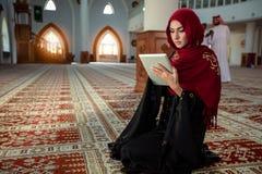 Молодая мусульманская женщина моля в мечети с Кораном на таблетке стоковые изображения rf