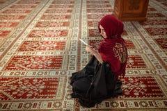 Молодая мусульманская женщина моля в мечети с Кораном на таблетке стоковые фото