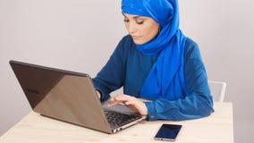 Молодая мусульманская женщина сидя в офисе и работая на компьтер-книжке видеоматериал