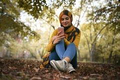 Молодая мусульманская женщина сидя в природе используя умный телефон Стоковое фото RF