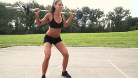 Молодая мышечная женщина делает тренировки со штангой сток-видео