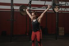 Молодая мышечная женщина делая тренировки поднятия тяжестей на спортзале crossfit стоковое изображение rf