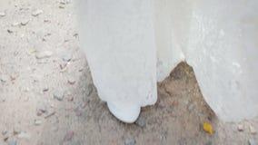 Молодая невеста в белых ботинках и длинном платье свадьбы на скалистом асфальте акции видеоматериалы