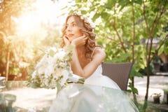 Молодая невеста сидит на стеклянном столе при ее руки сложенные на подбородке borehole стоковое изображение