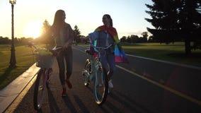 Молодая однополая пара идя с велосипедами outdoors акции видеоматериалы