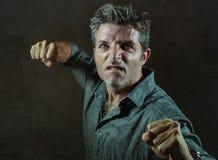 Молодая осадка и агрессивный человек в пабе поднимая пунш кулака угрожая бросая готовый для боя как жестокий нарушитель спокойств стоковое фото