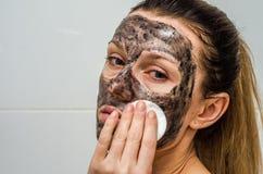 Молодая очаровательная девушка делает черную маску угля на ее стороне Стоковая Фотография RF